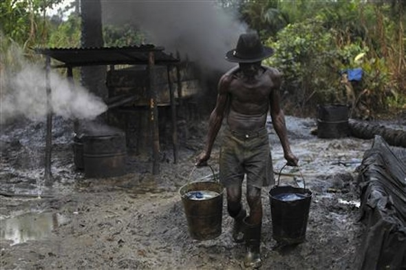 Ebiowei, 48, carries refined oil in buckets at an illegal oil refinery site. Credit: REUTERS/Akintunde Akinleye